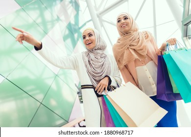Beautiful girlfriends smile while walking in the mall. Woman showing something to her friend in the mall.