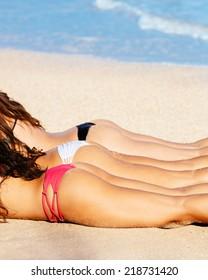Beautiful Girls in Bikinis Sunbathing on the Beach. Summer fun lifestyle.
