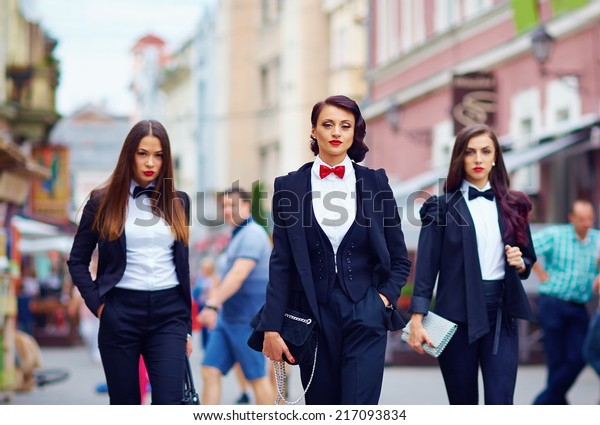 beautiful girls in black suits walking the street
