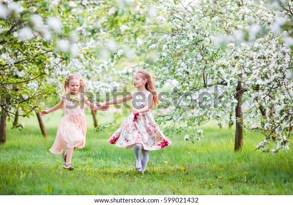 Beautiful girls in blooming apple tree garden enjoy warm spring day