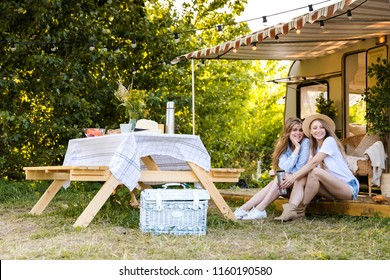 Beautiful girls by the van in a camping near a table with lunch. Travel, natural life, adventure