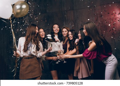 Beautiful girls celebrate New Year. Enjoying carefree time together. Group of beautiful young girl throwing gold confetti and looking happy and drinking champagne