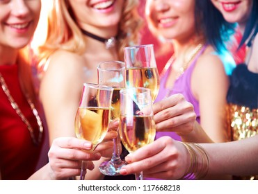 Beautiful girls clink glasses of champagne at a party. unrecognizable people