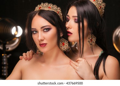 Beautiful girls in the crowns with perfect make up.  Woman whispering in her friend`s  ear a secret.