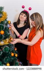 Beautiful girls decorate the Christmas tree. The Concept Of Christmas. Two girls decorate the Christmas tree.