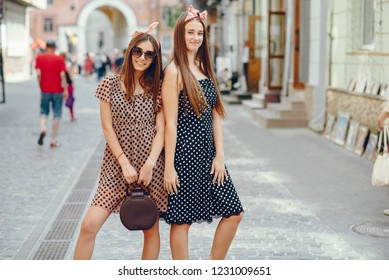 Beautiful girls dressed in retro dress. A preety ladies with a tape on her head. Famale in a summer city