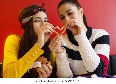 Beautiful girls eat burgers and french fries in the restaurant.