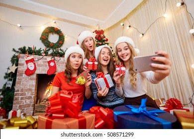 Beautiful girls, friends in caps of Santa Claus doing selfie mobile phone, laughing, smiling in Christmas room decoration new year.