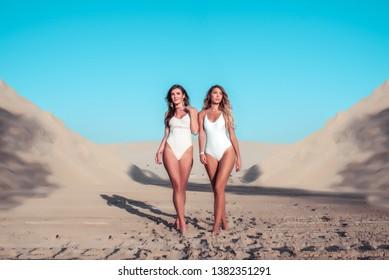 Beautiful girls girlfriends in white swimsuit bodysuit. Walk on sand. Sunbathe resting in nature. Girlfriends sisters walk. Emotions of happiness, smiles. Concept of a weekend getaway in nature.
