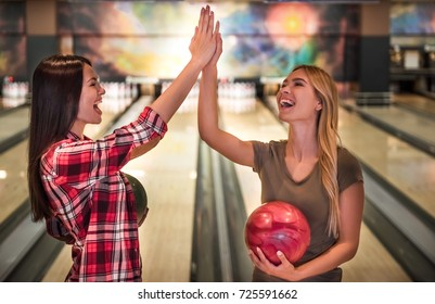 Beautiful girls are holding bowling balls, giving high five and smiling ready to play