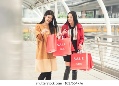 Beautiful girls holding sale bags shopping day walking on sky walk at the shopping mall.