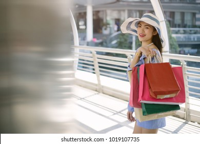 Beautiful girls are holding shopping bags, using a smart phone and smiling while standing street city background.