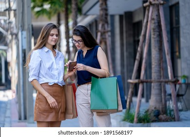 Beautiful girls holding shopping bags talking and checking way on smartphone in city,Shopping concept.