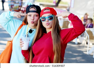 Beautiful girls in hoodies and cap enjoying their coffee. Young active people. Outdoors