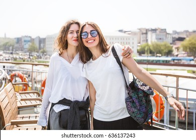 Beautiful girls hug and have fun.Girl friends,girl in white T-shirt,stylish girls,woman in sunglasses,happy face,stylish bag,curly hair,happy face,laugh,emotions,spring vacations,friendly,attractive