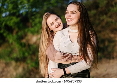 Beautiful girls hug, smile and relax in nature