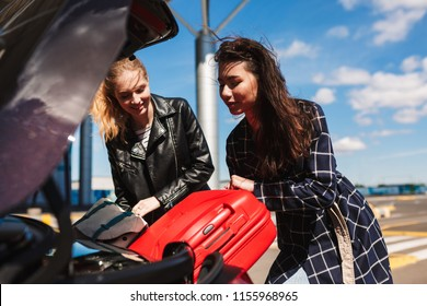 Beautiful girls joyfully folding suitcases together into trunk of black car near airport