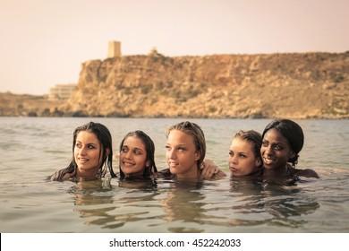 Beautiful girls looking away at the seaside