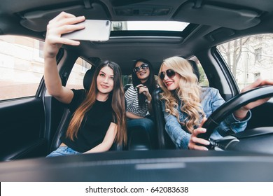 Beautiful girls are making selfie, looking at camera having fun while sitting in the car