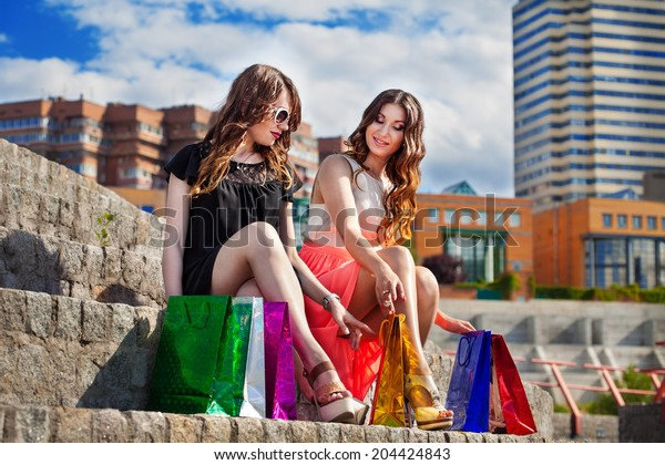 Beautiful girls with many shopping bags in city. Shopping and tourism concept