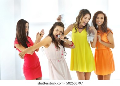 Beautiful girls with microphone on light background