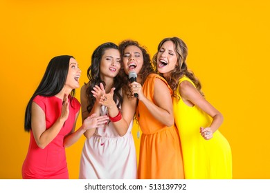 Beautiful girls with microphone on yellow wall background