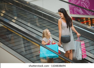 Beautiful girls mother and daughter in the shopping mall. Young mom and her little pretty child shopping together. Cheerful family buying goods on a sale