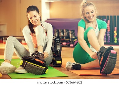 Beautiful girls preparing for Kangoo Jumping training in the gym.