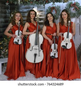 Beautiful girls in red dresses with violins for the new year