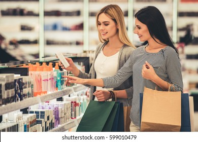 Beautiful girls with shopping bags are choosing cosmetics and smiling while doing shopping in the mall