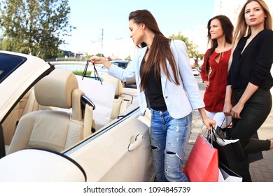 Beautiful girls with shopping bags discussing purchases and smiling while leaning on their car