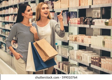 Beautiful girls with shopping bags are smiling while doing shopping in the mall
