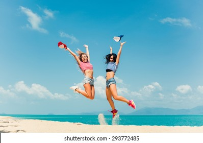 beautiful girls in shorts and bikinis and sunglasses fun walk on the beach and smiling best friend having fun jumping lifting his arms up