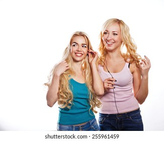 Beautiful girls sisters headphones listening to music with fluttering hair