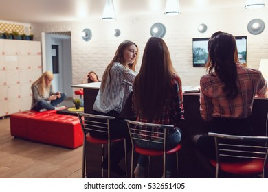 Beautiful girls sitting at the bar in Hostel, watching tv and talk.