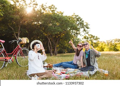 Beautiful girls sitting on picnic blanket with little dog and happily taking photos on white polaroid camera spending time on picnic in park with red bicycle on background