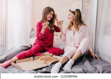Beautiful girls in socks and pajamas talking around and joking. Indoor portrait of positive ladies eating pizza in bed.
