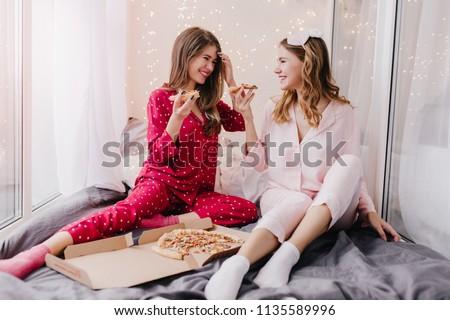 c1dff363c3dd Beautiful girls in socks and pajamas talking around and joking. Indoor  portrait of positive ladies