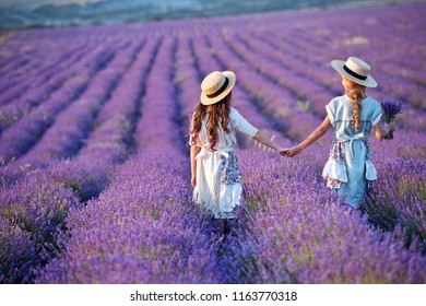 Beautiful girls  in straw hat on the lavender field on sunset. Girls collect lavender. Girlfriend in vintage dresses.