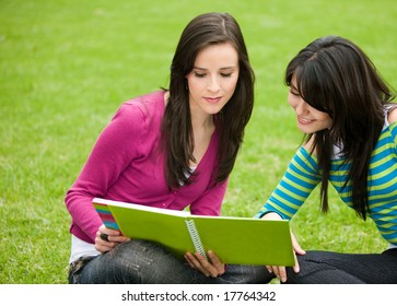 Beautiful girls studying with their notebooks - smiling outdoors
