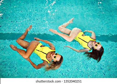 beautiful girls in sunglasses and bright swimsuits, athletes in synchronized swimming do a show and show in the pool