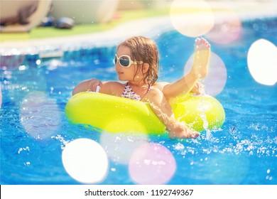 Beautiful girls at swimming pool in summer