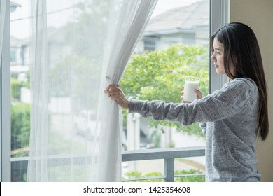 Beautiful Girls Teenage Drinking Fresh milk Coffee In the house window in the morning holiday Wearing gray pajamas After waking up bright Happy for health breakfast Asia