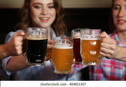 Beautiful girls and their friends drinking beer in pub