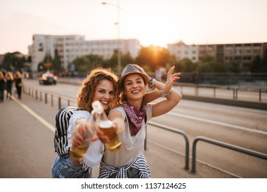 Beautiful girls toasting with drinks in the city street.