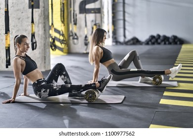 Beautiful girls are training with black-yellow foam rollers on the gray mats in the gym. They are wearing the multicolored sportswear: pants, tops and sneakers. Women are looking forward. Horizontal.