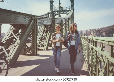 beautiful girls traveling, walking on a bridge while they are enjoying the beautiful view of the city
