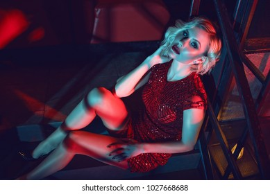 Beautiful glam blond woman with provocative make up wearing red short fitted sequin dress sitting on the stairs in the night club in colourful neon lights. Text space