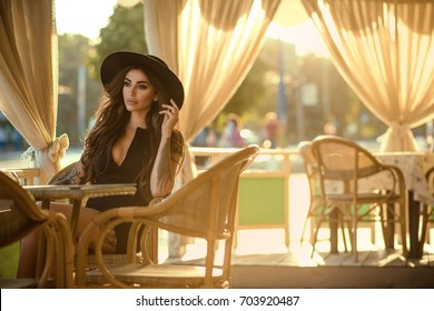 Beautiful glam tattooed brunette in little black dress and trendy fedora hat sitting in the nice open air summer restaurant in the city at sunset and looking aside with sadness in her eyes. Copy-space
