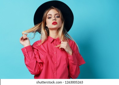 beautiful glamor woman in black hat in pink shirt on blue background